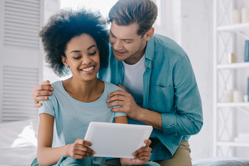 Young man and woman looking at tablet screen at home