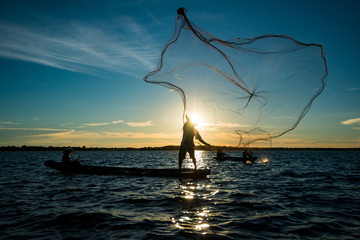 Un-identified silhouette fisher man on boat fishing by throwing fishing net