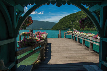 Pier with flowers on the Annecy Lake with blue sky mountains landscape. Near the lovely village of Talloires. Department of Haute-Savoie, southeastern France.