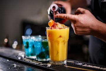 Bartender is preparing orange cocktail