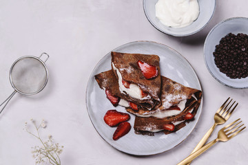 Homemade chocolate crepes with strawberry and cream on grey concrete background. Delicious breakfast. Selective focus