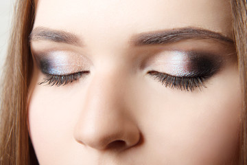 Professional make-up on closed eyes close-up. Bright female make-up.