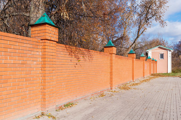 Red brick fence with a pink house