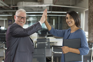 Two happy business colleagues giving high five after successful project start. Smiling mature man and young Indian woman posing in modern coworking space. Business success and teamwork concept