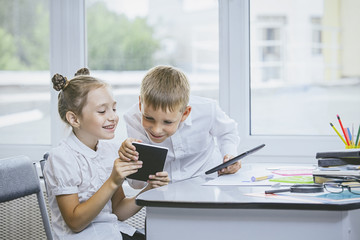 Beautiful children are students together in a classroom at the school receive education with tablets happy