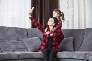 Beautiful happy family mother and daughter smile making selfie on mobile phone on the sofa in the living room