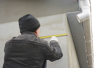 Contractor measuring wall before installing roof gutter downspout pipe.