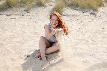 Hübsche rothaarige Frau sitzt lachend an einem Strand und lässt Sand durch ihre Finger rieseln