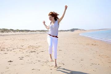 Hübsche rothaarige Frau läuft hüpfend über an einem Strand