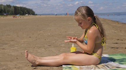 The girl apply sunscreen to face and body. The girl squeezes the sunscreen into her palm and puts it on her feet.
