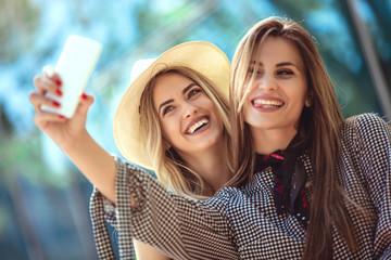 Two female friends taking a selfies, having fun outdoor