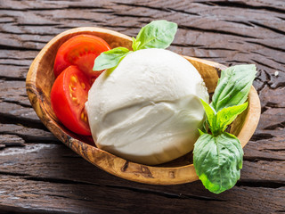 Buffalo mozzarella in the wooden bowl on the table.