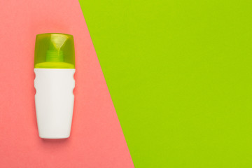 Cosmetic product on a bright bicolor background, top view