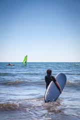 Surfer girl entering the sea