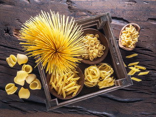 Different pasta types on the wooden table. Top view.