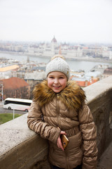 young little girl in hat and jacket is standing and smiling on parliament background from the fisherman bastion  in Budapest beautiful view