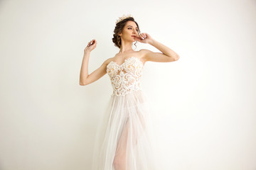young brunette sexy girl in a white wedding boudoir dress and gold crown in hairstyle is standing with hands near head like swan princess on a white wall background