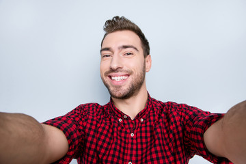Close up portrait of cheerful excited carefree restless active positive amusing guy with toothy beaming smile having a video chat via internet on holidays, isolated on gray background