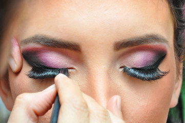 Make-up Applying closeup. Eyeliner. Cosmetic Eyeshadows. Beautiful young woman in beauty salon