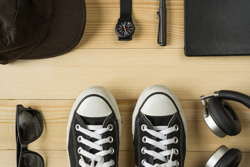 Top view of black canvas sneakers and black accesories on wooden background, casual clothes concept