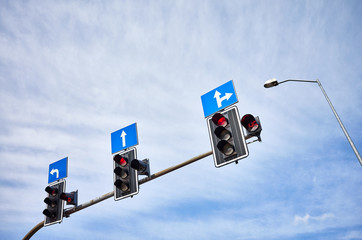 Traffic lights with countdown timers, red color displayed against the blue sky, space for text.