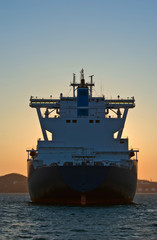 Rear view of a large LNG tanker standing in the roadstead at sunset.