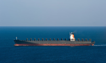 Empty container ship moving by sea.