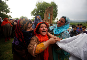Relatives mourn as they watch the body of Umar Kumhar during his funeral at Pinjora village in Kashmir's Shopian district