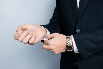 Cropped close up photo of businessman's hands correcting cufflincs on white shirt, wearing black formal outfit, isolated on gray background