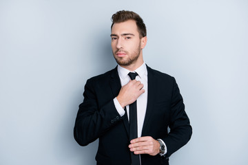 Portrait of handsome attractive serious wealthy bearded guy correcting narrow modern fashionable black tie with hands, isolated on gray background,  copy-space