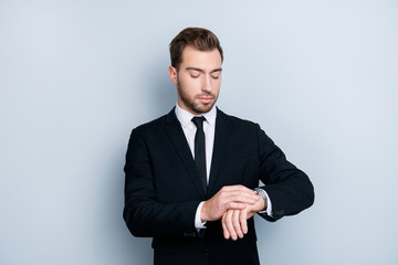 Portrait of confident smart clever fashionable successful wealthy wearing black formal outfit and trendy white shirt lawyer, he is checking time om his silver wristwatch, isolated om gray background