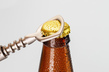 A hand opening a fresh cold ale bottle of beer with drops and stopper open with bottle opener on white background.