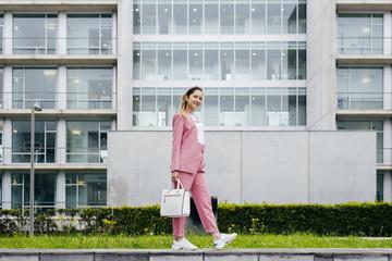 Stylish model in pink on street
