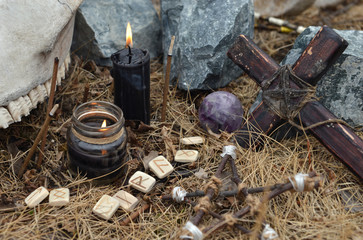 Wooden cross, old runes, pentagram and black candles. Mystic background with ritual esoteric objects, occult and halloween concept