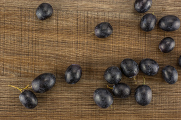 Black grape berries (autumn royal variety) table top isolated on brown wood background.
