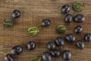 Black grape berries (autumn royal variety) table top isolated on brown wood background some sliced.