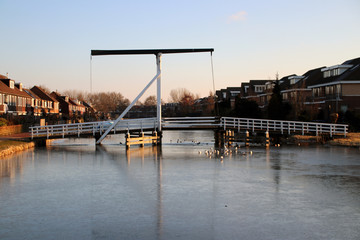 White wooden drawbridge in the center of village  Nieuwerkerk aan den IJssel over the ring canal Zuidplaspolder with ice in the morning sun