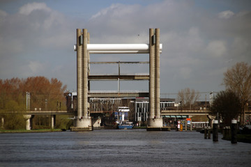vertical lift bridge for trains in Gouda opens for a freight ship on canal named Gouwe.