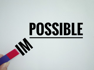 Conceptual - 'POSSIBILE ' written on a white paper with letter 'IM' being pulled away from it using a magnet. Vintage styled background.