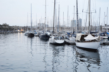 Boats in the port of Barcelona. Nice picture of the mediterranean sea in Catalonia, Spain. Several types of sailboats are seen and reflected in the water on a cloudy autumn afternoon.