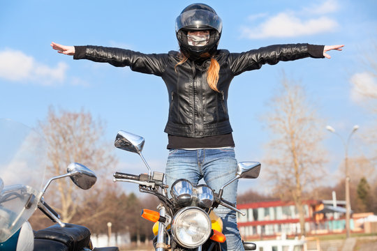 Stunt girl balancing while riding motorcycle without hands, arms extended sidewards