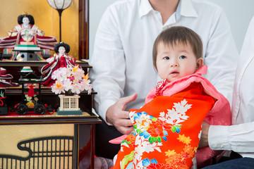 初節句で両親に抱かれる赤ちゃん