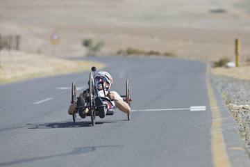 Disabled racing cyclist riding recumbent bicycle on open road