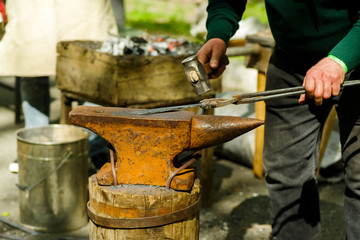 blacksmith with a hammer and an anvil working on a product on the street