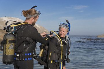 Diver checking partners ocean scuba equipment from rocky beach