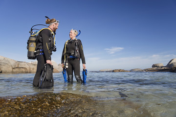 Couple in wetsuit going ocean scuba diving from beach