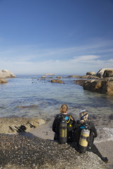 Couple in wetsuits going ocean scuba diving from rocky beach