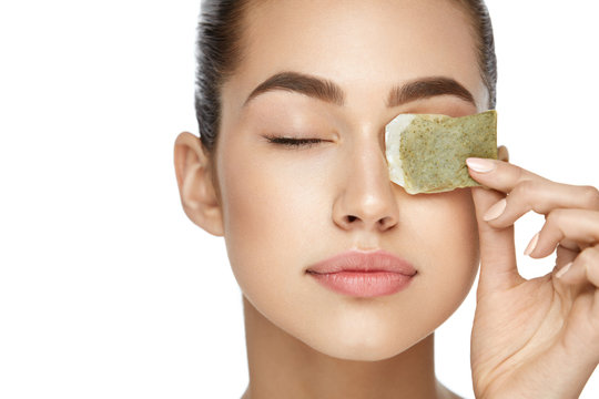 Eye Skin Care. Beautiful Woman With Green Tea Bag Under Eyes