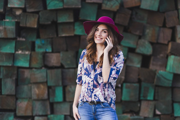 portrait of a young beautiful woman wearing casual clothes and a modern hat and talking on her mobile phone. She is standing over green wood blocks background and smiling. Outdoors lifestyle.