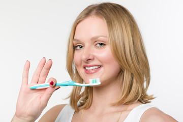 Junge hübsche Frau mit einer Zahnbürste in der Hand lächelt